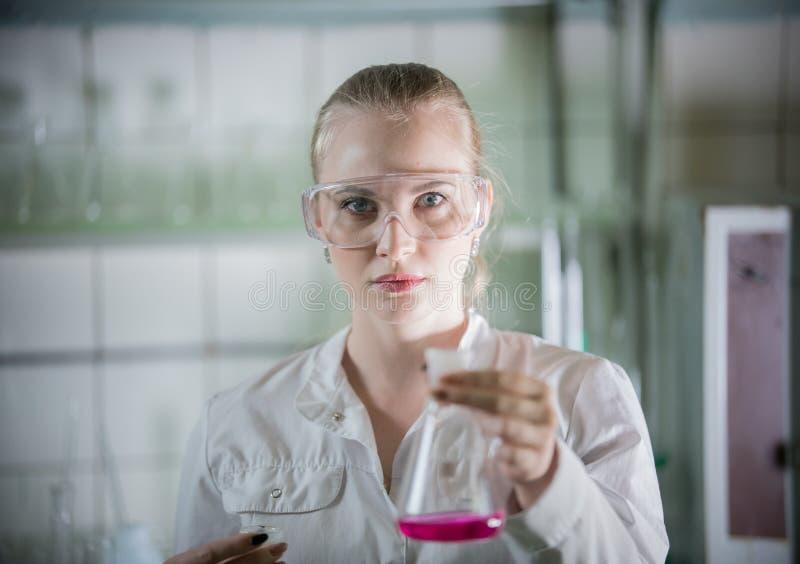 化工实验室 拿着有液体的年轻白肤金发的妇女一个烧瓶在它 库存照片