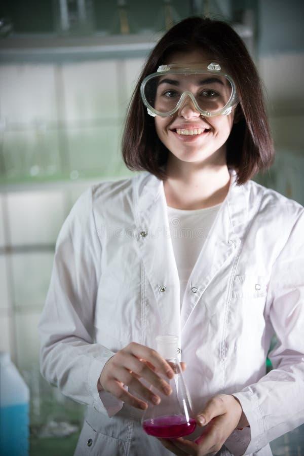 化工实验室 看在照相机的工作玻璃的年轻微笑的妇女 免版税库存照片