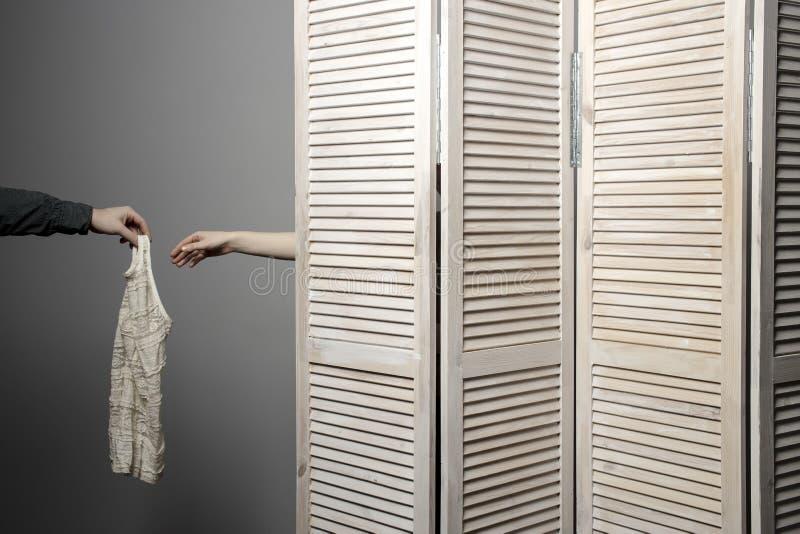 化装室摊位的妇女,人的手递交礼服 库存图片