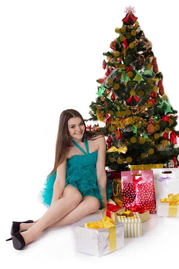 化装舞会服装下面圣诞树的俏丽的女孩 免版税图库摄影