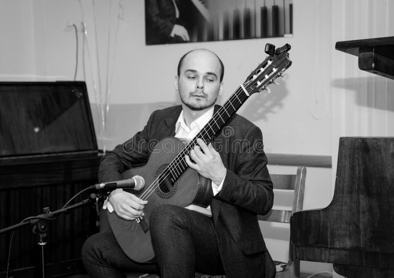 北京,中国黑白照片 音乐家激动在他的弹吉他的面孔的 库存图片