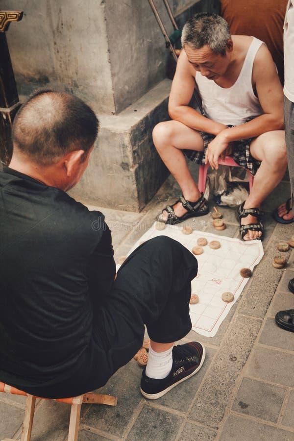 北京,中国12/06/2018两个中国领抚恤金者热心地打在街道上的传统中国下棋比赛 库存图片
