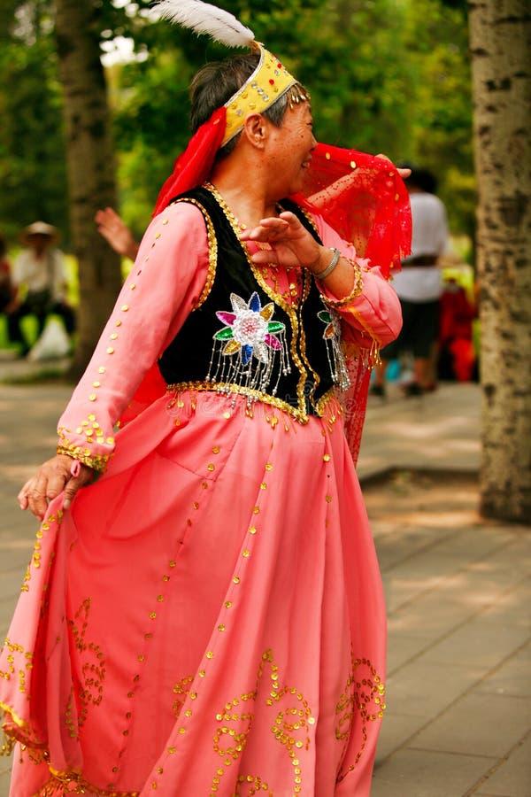 北京,中国07 06 2018红色礼服舞蹈的愉快的妇女在公园 免版税图库摄影