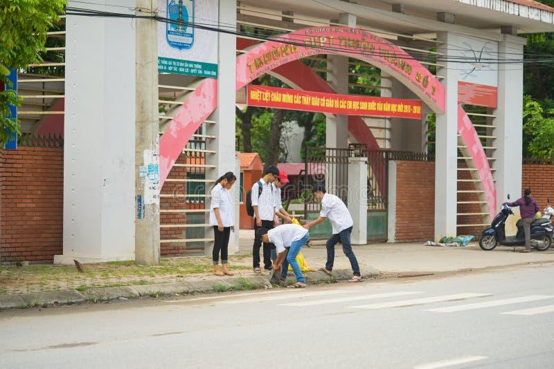 北宁市,越南- 2015年9月9日:小组清洗在他们的学校前面的高中学生街道在志愿事件内 库存照片