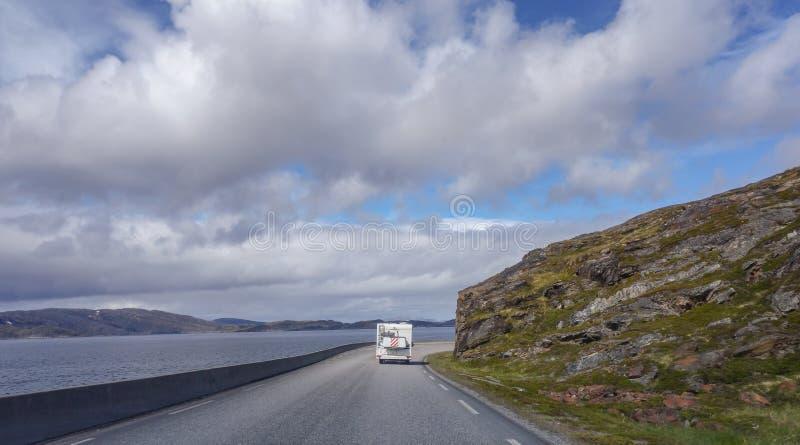 北挪威,在导致亨墨菲斯的狭窄和有风路的露营者货车在一个晴天 库存照片