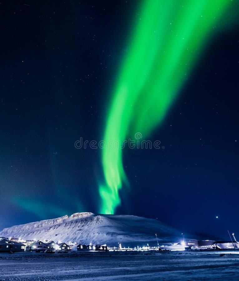 北极光在斯瓦尔巴特群岛,朗伊尔城市,卑尔根群岛,挪威墙纸山房子里  图库摄影