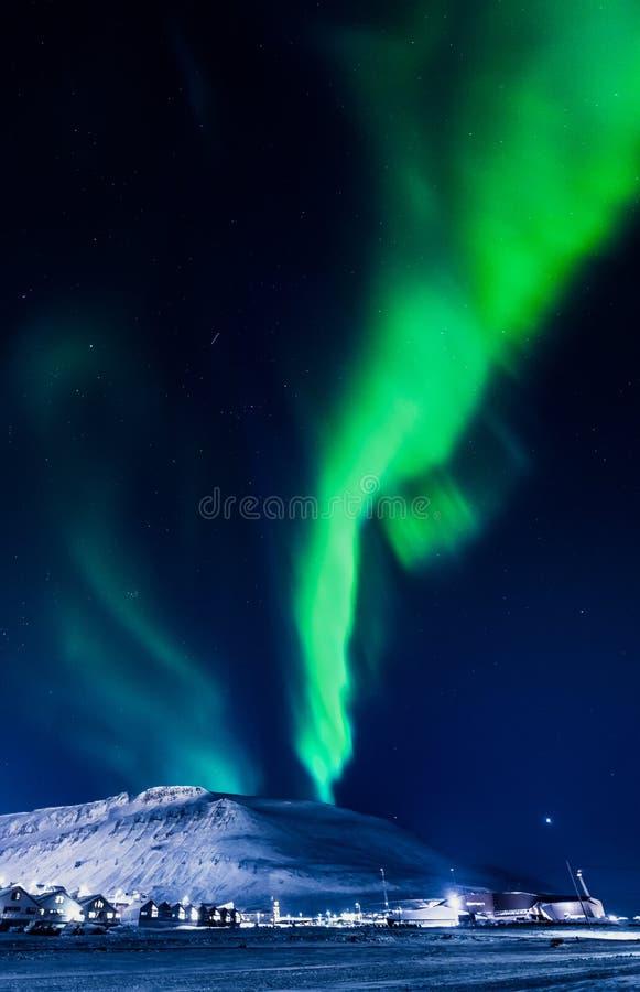 北极光在斯瓦尔巴特群岛,朗伊尔城市,卑尔根群岛,挪威墙纸山房子里  免版税图库摄影