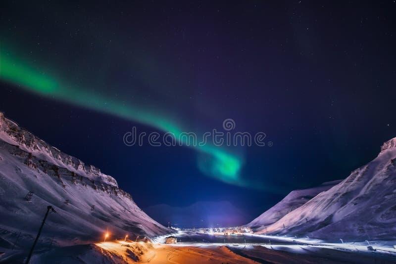北极光在斯瓦尔巴特群岛,朗伊尔城市,卑尔根群岛,挪威墙纸山房子里  免版税库存图片