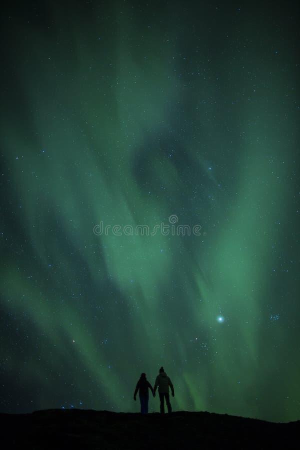在蜜月夫妇之上的北极光 库存照片