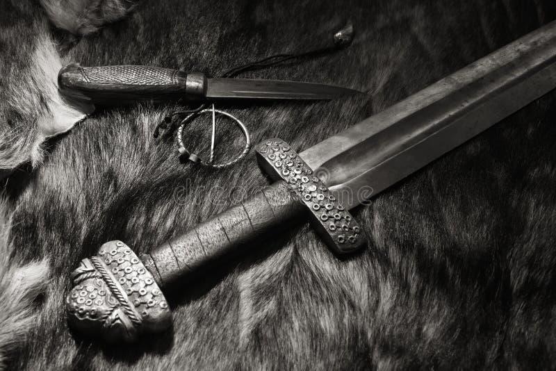 北欧海盗剑和刀子在毛皮 库存图片