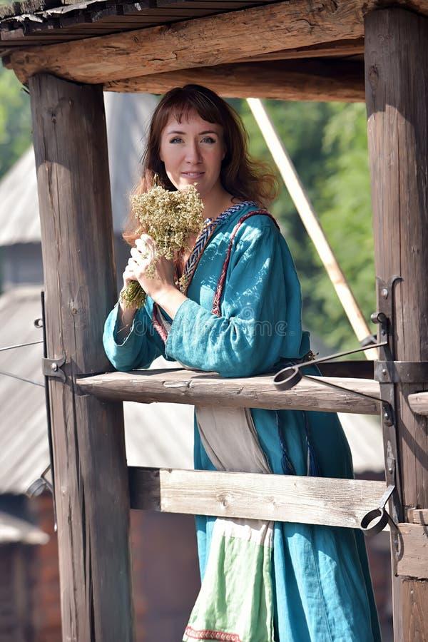 北欧海盗妇女,一件蓝色亚麻制礼服的浅黑肤色的男人, 库存图片