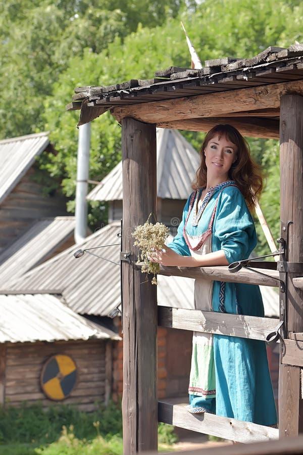 北欧海盗妇女,一件蓝色亚麻制礼服的浅黑肤色的男人, 免版税库存照片