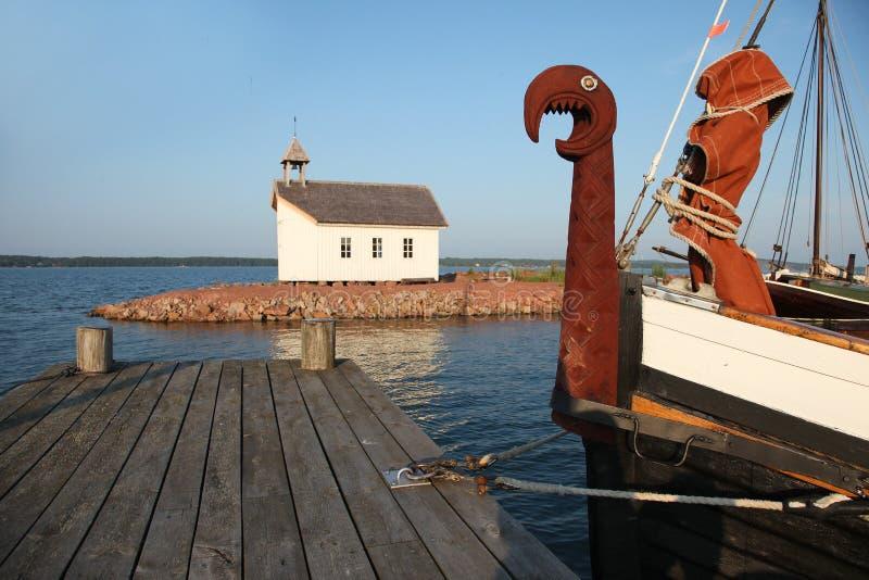 北欧海盗小船和教堂在造船厂在Marienhamn 库存图片