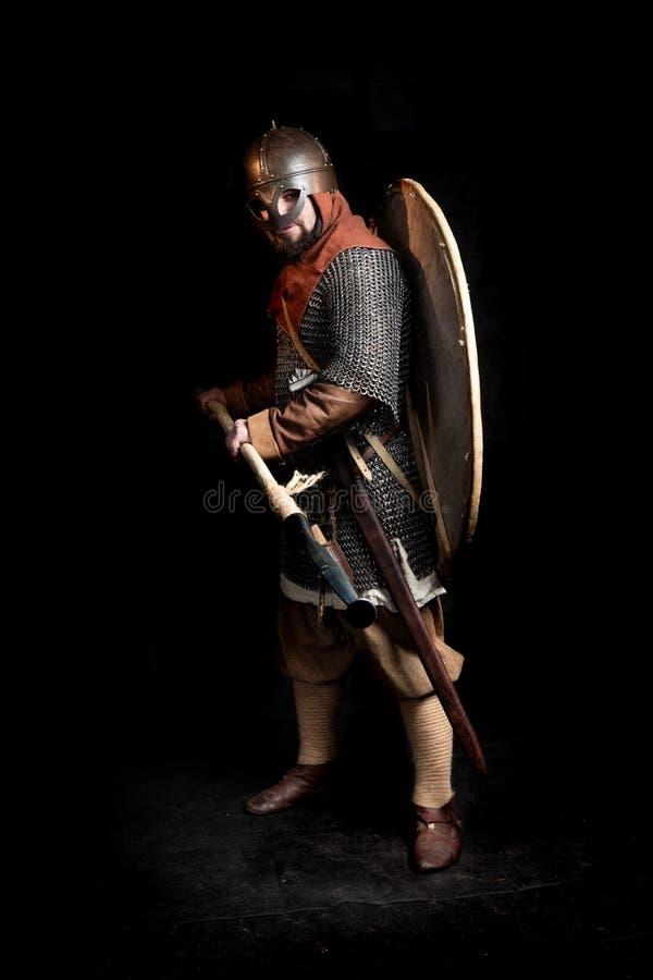 北欧海盗年龄的装甲的有胡子的战士拿着一把长矛和剑 免版税库存图片