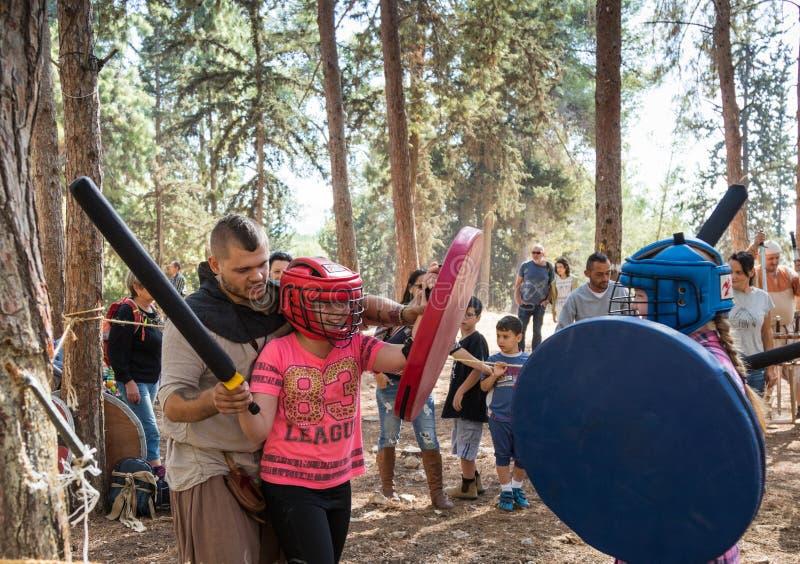 `北欧海盗村庄`的重建参加者在森林里教swordfighting在阵营的孩子在本Shemen附近  免版税库存图片