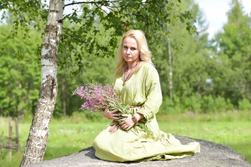 北欧海盗的葡萄酒衣裳的金发碧眼的女人坐与野花i 免版税库存图片