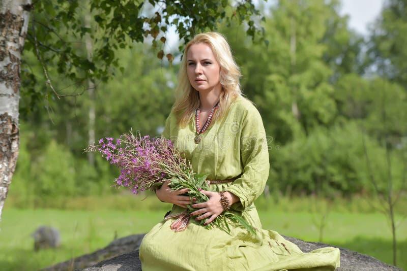 北欧海盗的葡萄酒衣裳的金发碧眼的女人坐与野花i 图库摄影