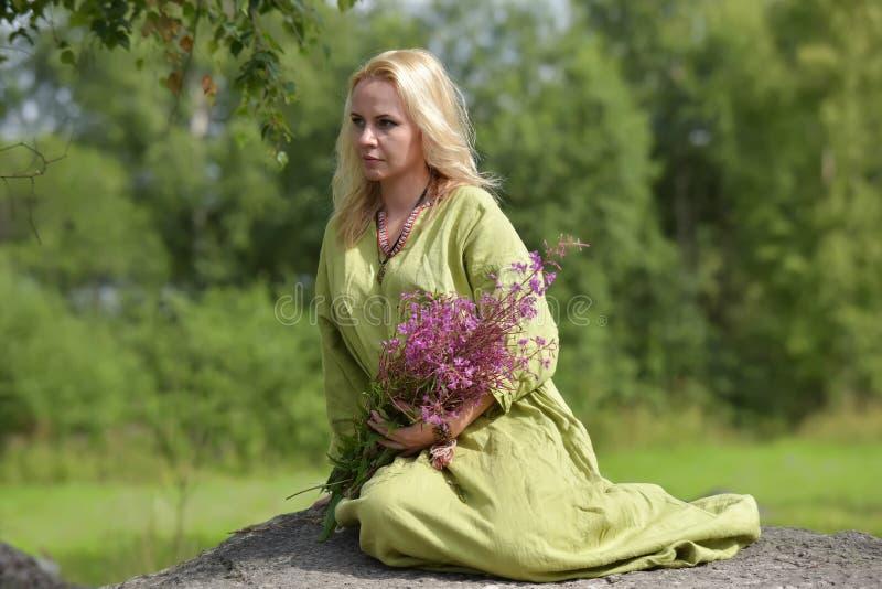 北欧海盗的葡萄酒衣裳的金发碧眼的女人坐与野花i 库存图片