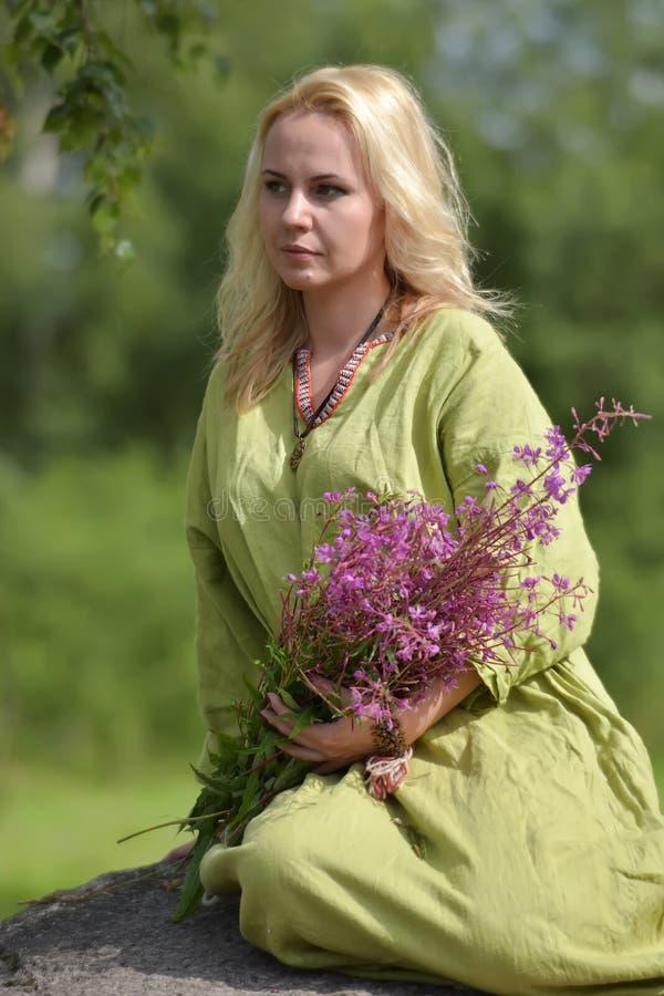 北欧海盗的葡萄酒衣裳的金发碧眼的女人坐与野花i 库存照片