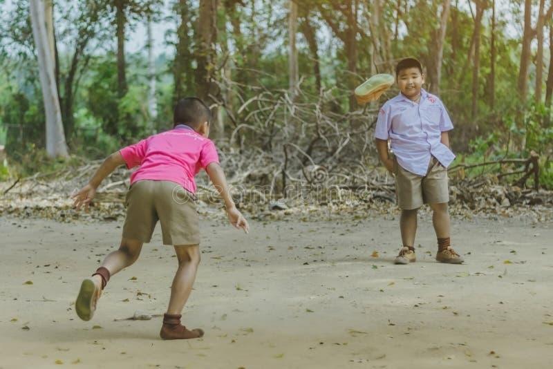 北碧泰国- 2月2日:不明身份的学生在学校喜欢踢与他们的朋友的老橄榄球在地面上 图库摄影
