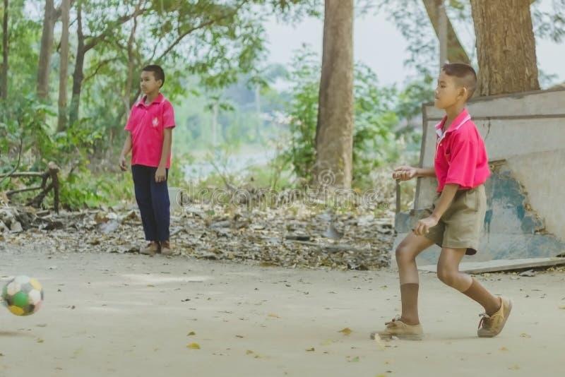 北碧泰国- 2月2日:不明身份的学生在学校喜欢踢与他们的朋友的老橄榄球在地面上 免版税图库摄影