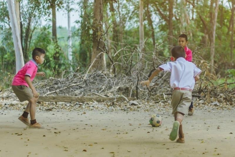北碧泰国- 2月2日:不明身份的学生在学校喜欢踢与他们的朋友的老橄榄球在地面上 库存照片