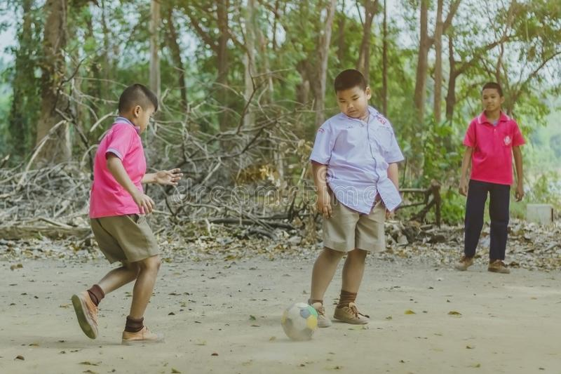 北碧泰国- 2月2日:不明身份的学生在学校喜欢踢与他们的朋友的老橄榄球在地面上 免版税库存图片
