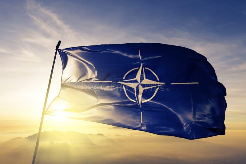 北约组织北约OTAN旗子纺织品挥动在顶面日出薄雾雾的布料织品 向量例证