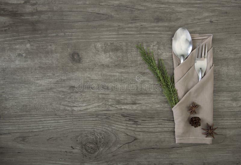 匙子和叉子与餐巾设置在木台式视图 免版税库存照片