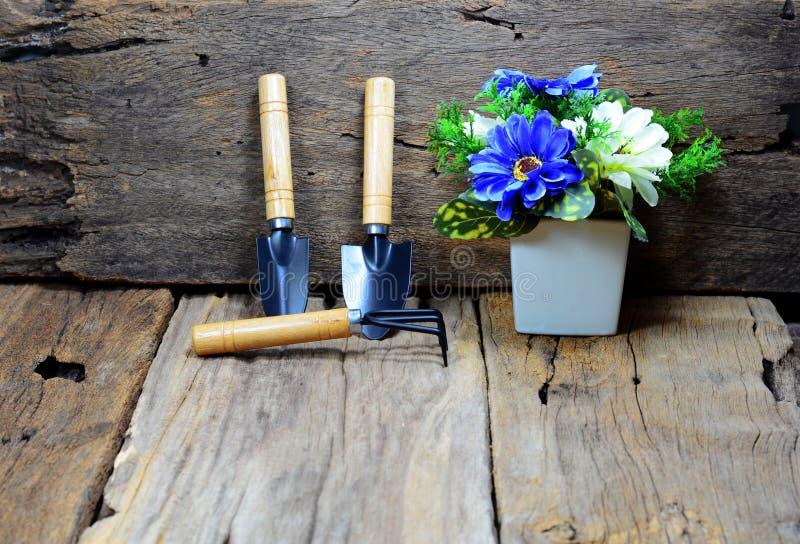 匙子和叉子从事园艺的倾斜的反对与老木头 免版税库存照片