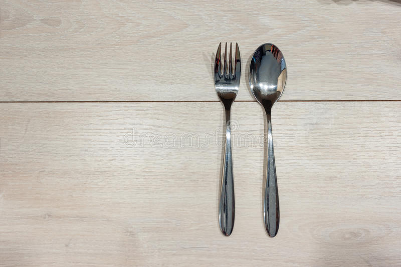 匙子和叉子在一张木桌上 免版税库存照片