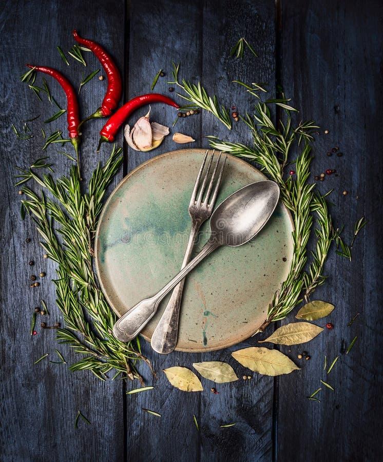 匙子和叉子在板材有草本和香料框架的在深蓝木桌上 免版税库存图片
