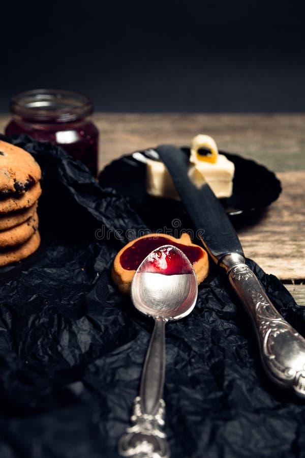 匙子用在巧克力曲奇饼和饼干附近的果酱在黑桌背景 下午断裂时间 早餐 图库摄影