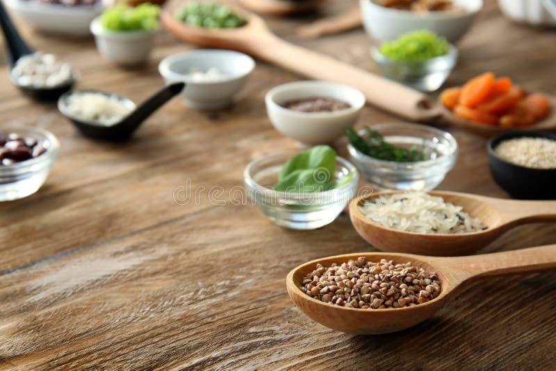 匙子用荞麦和保健品在木桌上 免版税库存照片