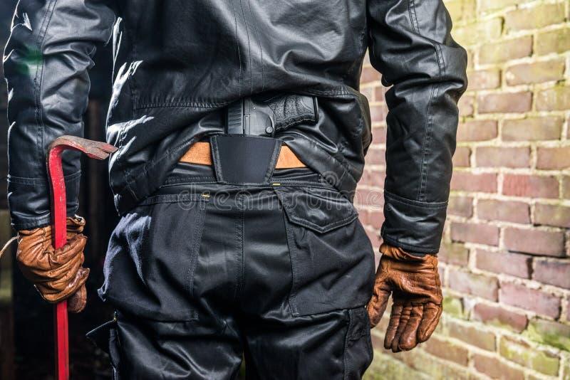 匪徒中央部位背面图有站立b的撬杠和枪的 免版税库存图片