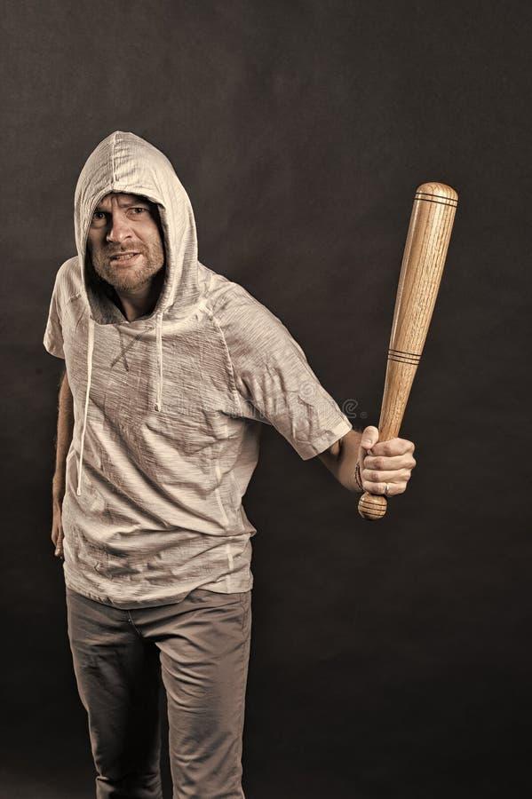 匪徒人威胁与棒武器 有胡子的人举行棒球棒 小流氓在有冠乌鸦T恤杉的穿戴敞篷 侵略或 免版税库存图片