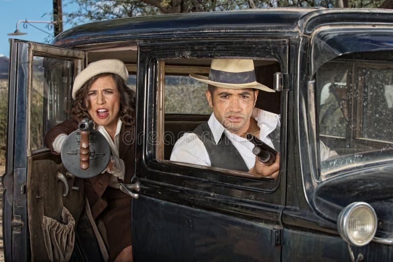 匪徒妇女从汽车的生火枪 免版税库存照片