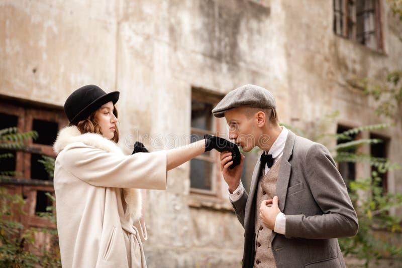 匪徒 以一个被放弃的大厦为背景在森林,一个人亲吻一只妇女` s手 免版税图库摄影