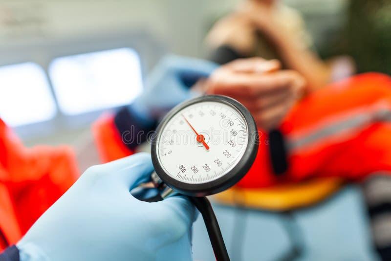 医务人员检查患者的血压 图库摄影