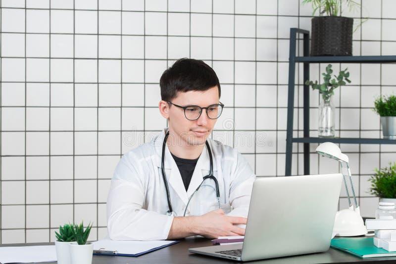 医学、行业、技术和人概念-有膝上型计算机的微笑的男性医生在医疗办公室 免版税图库摄影