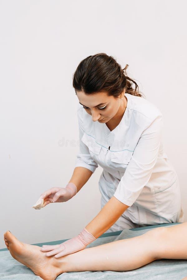 医学专家执行一名妇女的腿的糖epilation发廊的 库存照片