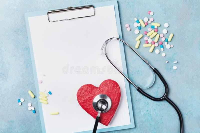 医学剪贴板、听诊器、药物药片和心脏红色形状在蓝色背景顶视图的 健康和心脏病学概念 免版税库存照片