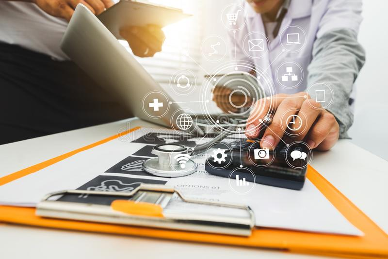 医学医生手与现代计算机和巧妙的电话,有他的队的数字式片剂一起使用在白色书桌上 库存照片