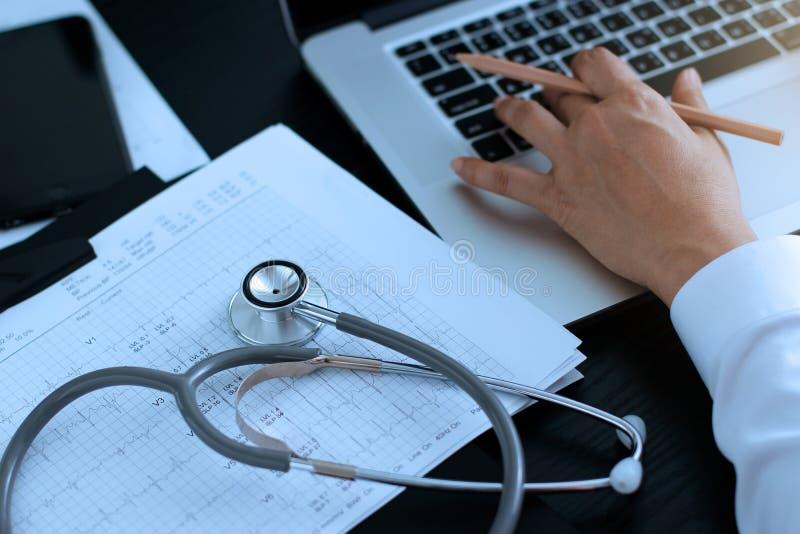 医学医生 有心跳报告的听诊器,分析在膝上型计算机的核对 免版税库存照片
