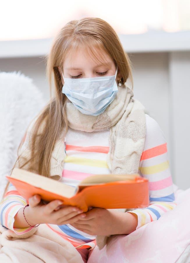 医学医疗保健面具的不适的小女孩读书的 免版税图库摄影