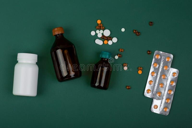 医学概念五颜六色的药片和医疗瓶在绿皮书背景 免版税库存图片