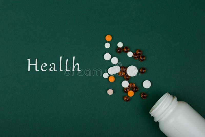 医学概念五颜六色的药片和白色医疗瓶在绿皮书背景 免版税库存图片
