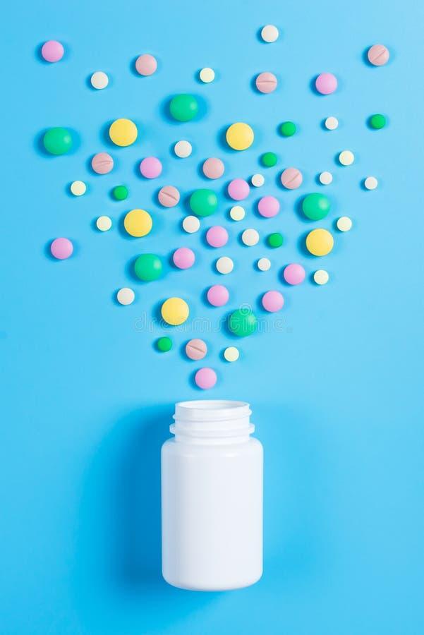 医学绿色,黄色和桃红色药片或胶囊和白色瓶在蓝色背景 免版税库存图片