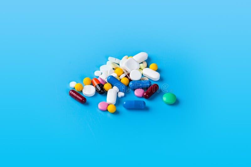 医学药片、片剂和胶囊在蓝色背景 库存图片