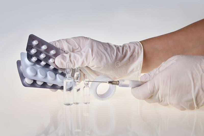 医护人员的手拿着注射器和片剂的白色手套的 免版税库存照片